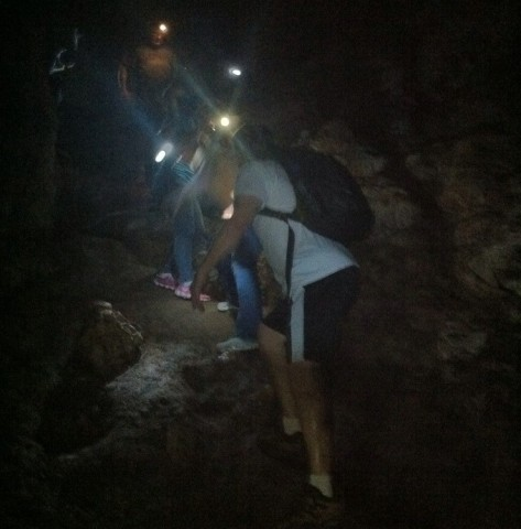 Hiking through a dry cave with headlamps.