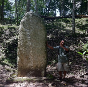 Tour guide with giant stone tribute to a former king of Caracol.